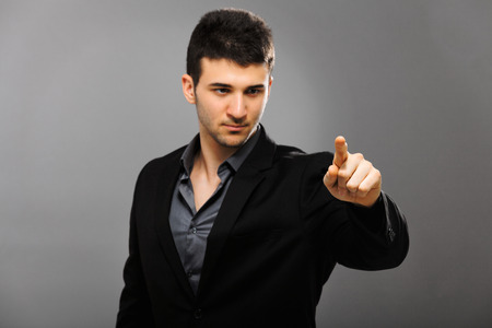 left hand: Young businessman pointing with his left hand, isolated on gray Stock Photo