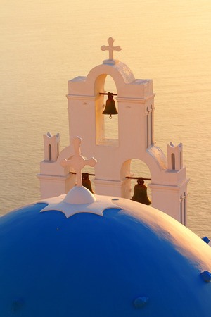 fira: Famous church in Fira, Santorini at sunset with a perfect view of the volcano