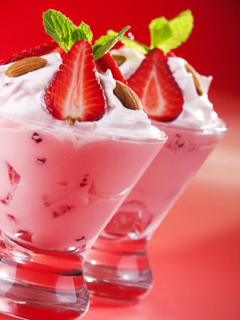 garnished: Strawberry cream in two glasses garnished with strawberries, almonds and fresh mint