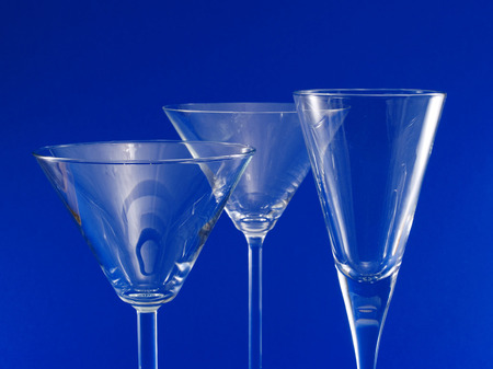 cocktail glasses: Three Empty Cocktail Glasses isolated on blue