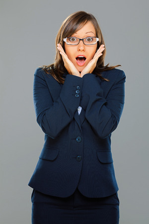 expressing: Businesswoman expressing surprise isolated on gray background