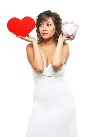 paper heart: Young attractive woman holding red paper heart like a valentine card and pink piggy bank