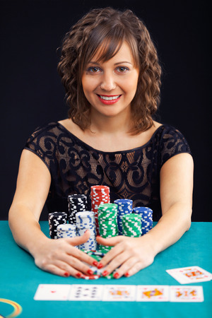 wideangle: Young woman holding gambling chips on black background Stock Photo