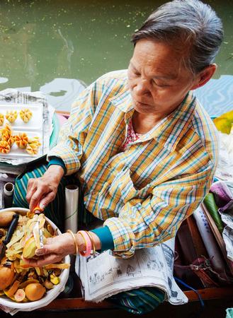 damnoen saduak: Damnoen Saduak, Thailand - March 21, 2011 : Senior Thai woman selling freshly cooked food and fruits on a boat in Damnoen Saduak Floating Market