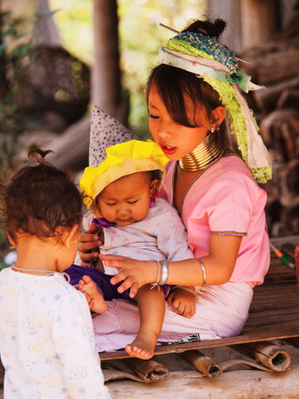 kilograms: Chian Mai, Thailand - March 07, 2011 : Street portrait of a young long-neck woman holding a baby and young boy. There are 25 copper rings on her neck weighting 9 kilograms.