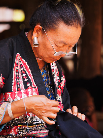 bamboo house: Chiang Mai, Thailand - March 07, 2011 - Portrait of 60 year old Thai woman, embroider a piece of cloth in front of her bamboo house