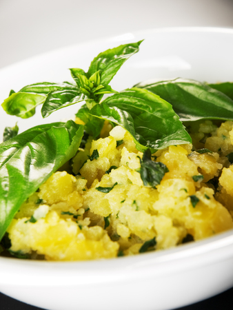 potato salad: Potato salad garnished with fresh basil Stock Photo