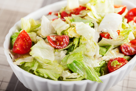 a portion: Salad with iceberg and cherry tomatos, one portion ready-to-eat