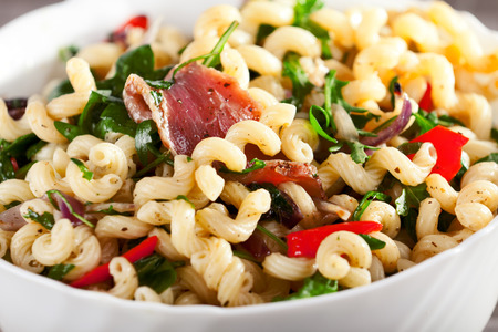rucola: Pasta with prosciutto, rucola and peppers in a big dish ready to be served Stock Photo