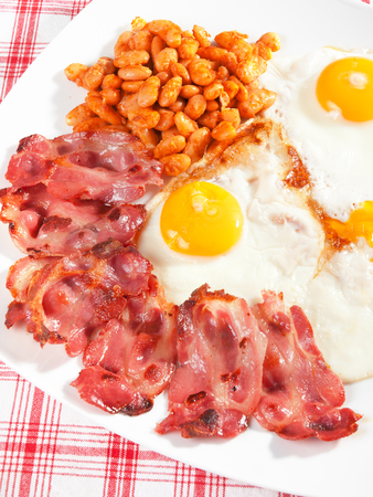english breakfast: Typical English breakfast with fried bacon, beans and eggs