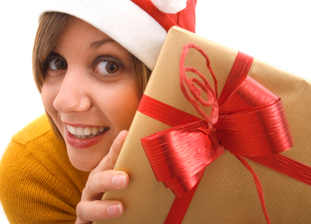 wideangle: Young girl with Christmas Hat holding a present isolated on white background Stock Photo