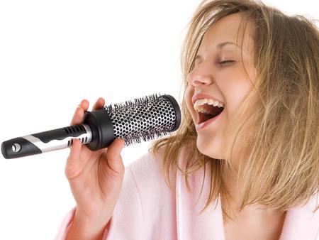 cantando: Mujer que canta con el cepillo para el pelo aislado en el fondo blanco