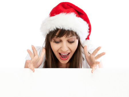 excited: Young excited woman with santa hat behind white billboard isolated on white background. Looking down. Stock Photo