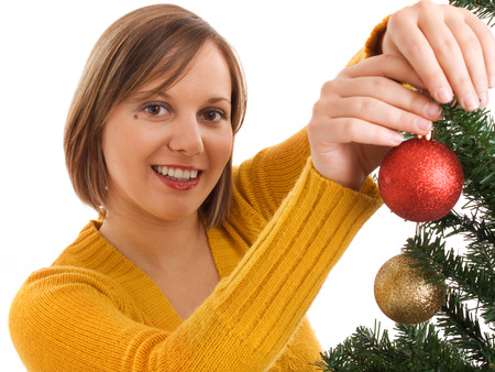 Young girl decorating Christmas tree with a red ball. Stock Photo