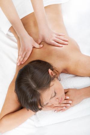 Junge Frau mit einem klassischen Massage auf weißen Bett