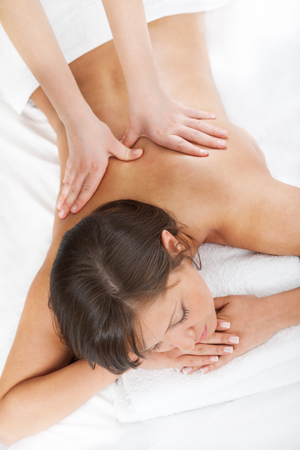 Young woman having a classical massage lying on white bed Stock Photo