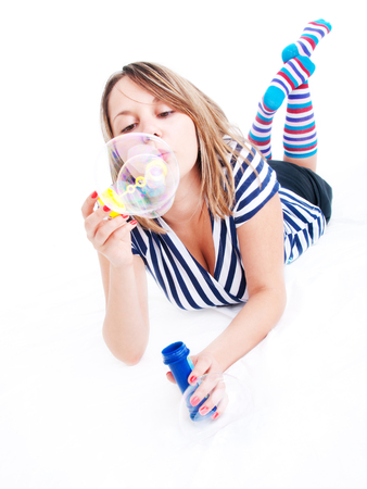 soap sud: Girl blowing bubbles, isolated on white