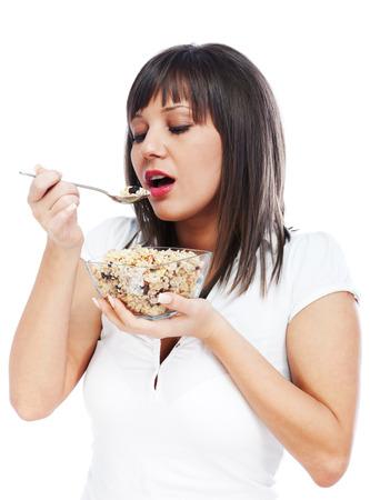 comiendo cereal: Mujer joven comer cereales para el desayuno, mirando a cámara, aislado en fondo blanco con espacio de copia