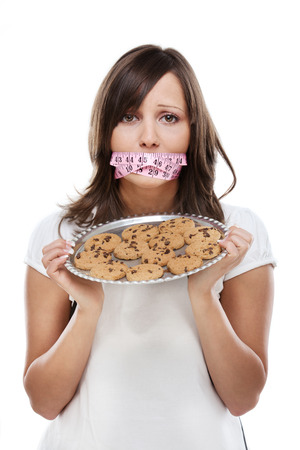 continence: Young woman holding a tray with homemade chocolate cookies and tied mouth with measuring tape, looking at camera