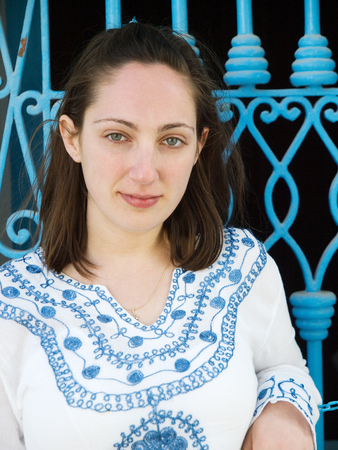 Young woman in tunisian clothes in front of a blue fence