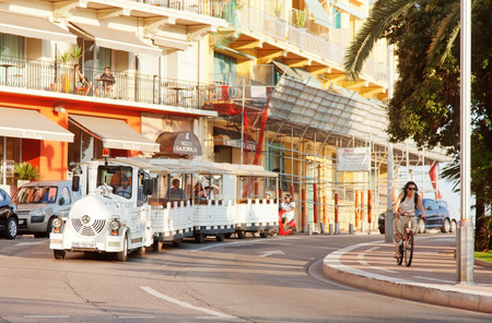 trackless: Nice, France - July 01, 2011 : Nice street live at sunset - white fun trackless train for sightseeing and one bicycle in front.