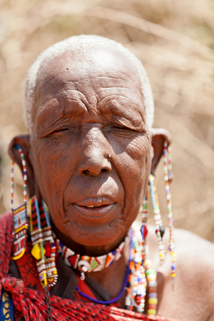 earing: Amboseli, Kenya - February 07, 2012 : Portrait of an old masai man with traditional earings and necklaces welcoming visitors to the masai village in Amboseli national park