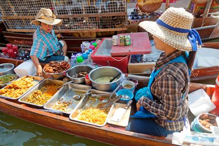 damnoen saduak: Damnoen Saduak, Thailand - March 21, 2011 : Two Thai women selling freshly cooked food and fruits on a boat in Damnoen Saduak Floating Market