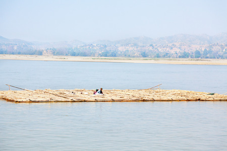 burmese: Mandalay, Myanmar - February 28, 2011 : One Burmese man carrying bamboo over Irrawaddy River