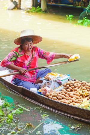 damnoen saduak: Damnoen Saduak, Thailand - March 21, 2011 : Senior Thai woman with hat selling fresh fruits on a boat in Damnoen Saduak Floating Market