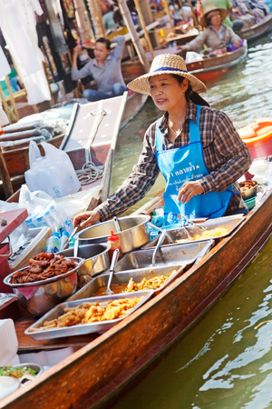 saduak: Damnoen Saduak, Thailand - March 21, 2011 : Young Thai woman selling freshly cooked food and fruits on a boat in Damnoen Saduak Floating Market