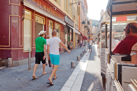 trackless: Nice, France - July 03, 2011 : Nice street live at noon - two men walking on the street. Photo taken from a trackless train