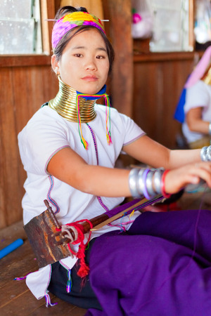 historical clothing: Chian Mai, Thailand - March 02, 2011 : Street portrait of a young long-neck woman weaving in a factory made of bamboo. There are 25 copper rings on her neck weighting 9 kilograms. She has the burden to wear them for life. Editorial