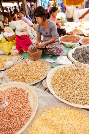 sitting on the ground: Heho, Myanmar - March 02, 2011 : Young Burmese woman selling nuts and beans at five-day market while sitting on the ground