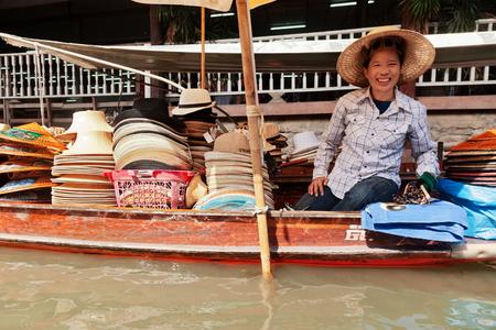 damnoen saduak: Damnoen Saduak, Thailand - March 21, 2011 : Thai woman selling hats on a boat in Damnoen Saduak Floating Market Editorial