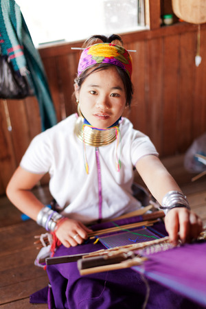 kilograms: Chian Mai, Thailand - March 02, 2011 : Street portrait of a young long-neck woman weaving in a factory made of bamboo. There are 25 copper rings on her neck weighting 9 kilograms. She has the burden to wear them for life. Editorial