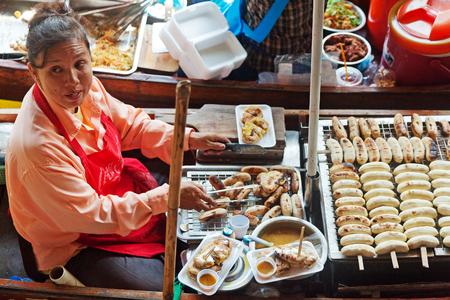 damnoen saduak: Damnoen Saduak, Thailand - March 21, 2011 : Thai woman selling freshly cooked food on a boat in Damnoen Saduak Floating Market