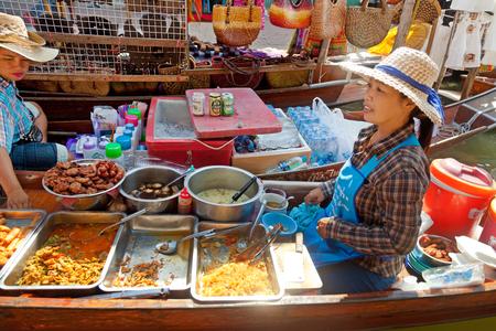 damnoen saduak: Damnoen Saduak, Thailand - March 21, 2011 : Young Thai woman selling freshly cooked food and fruits on a boat in Damnoen Saduak Floating Market