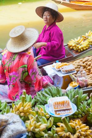 damnoen saduak: Damnoen Saduak, Thailand - March 21, 2011 : Senior Thai woman with hat selling fresh fruits on a boat talking to another woman in Damnoen Saduak Floating Market