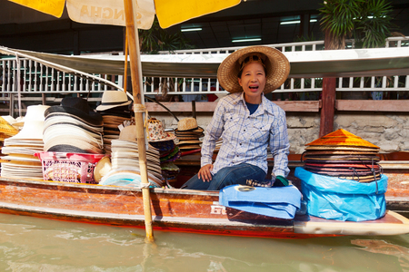 saduak: Damnoen Saduak, Thailand - March 21, 2011 : Thai woman selling hats on a boat in Damnoen Saduak Floating Market Editorial
