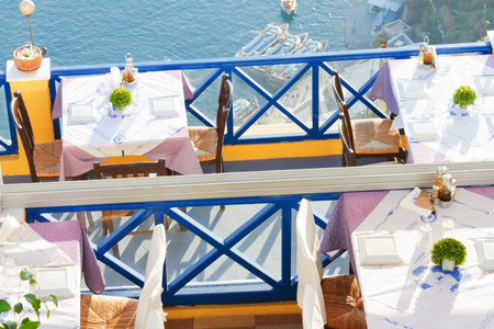dinner cruise: Fira, Greece - May 03, 2012 : Local restaurant with a seaview: an empty table with two chairs in the foreground, cruise ship in the background Editorial