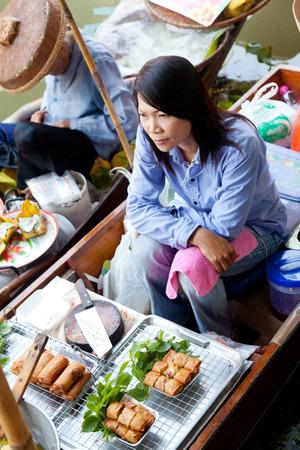 damnoen saduak: Damnoen Saduak, Thailand - March 21, 2011 : Young Thai woman selling freshly cooked food on a boat in Damnoen Saduak Floating Market