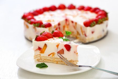 surface view: Cake with strawberries, gelly yogurt and cherries. Surface view. Isolated on white background. One piece in a white plate