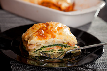 Typical Italian lasagna with spinach and salmon. Baking dish on background Standard-Bild
