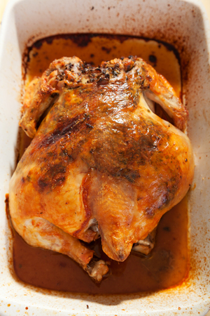whole chicken: Baked whole chicken with herbs in white caserole