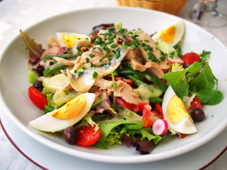 tilted view: Nicoise Salad served in a restaurant in Cannes, France. Horizontal, tilted view Stock Photo