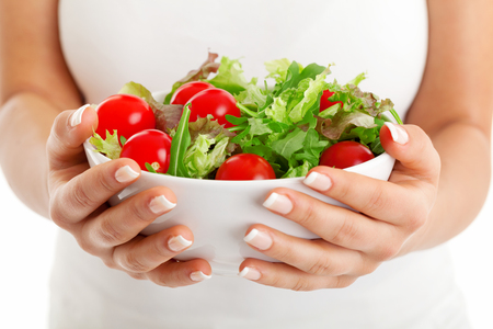 Salad bowl in woman hands isolated on white background
