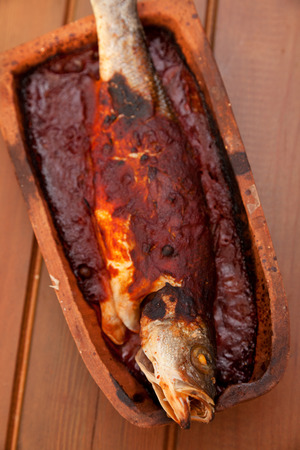 roof tile: Trout fish baked in roof tile with tomato sauce. Vertical shot Stock Photo