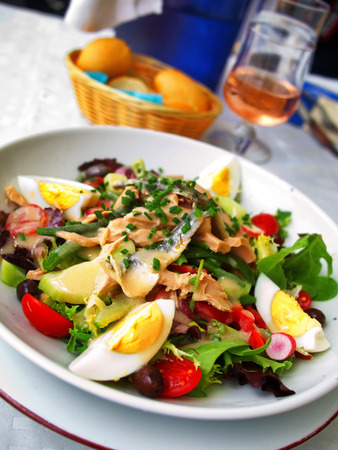 tilted view: Nicoise Salad served in a restaurant in Cannes, France. Tilted view with rose wine on background