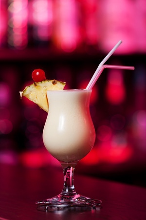 colada: Pina Colada cocktail shot on a bar counter in a nightclub in red light