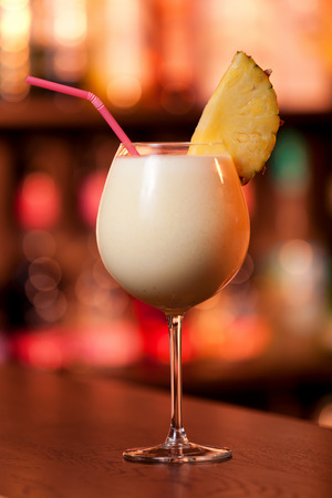 pina colada: Glass of Pina Colada cocktail shot on a bar counter in a nightclub in red light Stock Photo